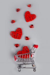Hearts and shopping cart on a grey background. Shopping for the holiday.